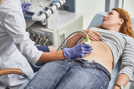 Expecting pregnancy. Doctor in white lab coat and sterile gloves examining red-haired woman with ultrasound scanner Stock Photo