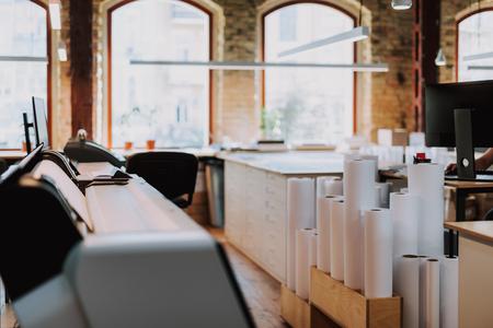 Rotoli di carta in piedi sul pavimento della tipografia con attrezzature moderne Archivio Fotografico