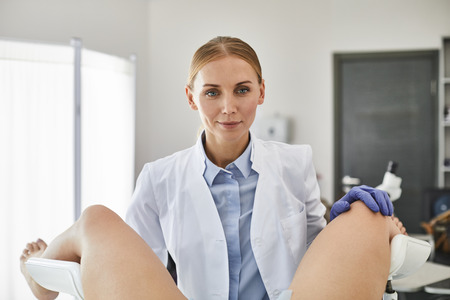 Waist up portrait of young doctor in white lab coat and sterile gloves doing gynecological test of woman