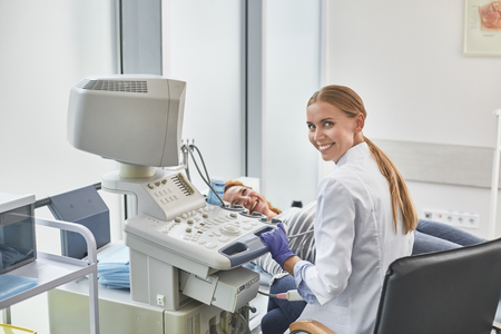 Back view portrait of gynecologist in white lab coat and sterile gloves using ultrasound scanner during medical examination of her patient. Smiling red-haired woman lying on daybed