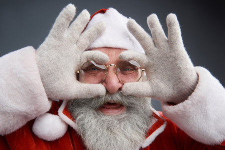 Messing around. Close up portrait of bearded old man in Santa costume touching spectacles and making funny face. Isolated on gray background