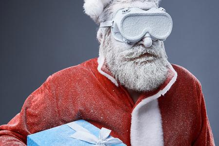 Retrato de estudio de anciano barbudo en traje de Santa cubierto de nieve. Él sostiene una caja de regalo azul con cinta. Foto de archivo