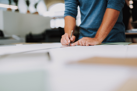 Close up of a male designer being involved in making a drawing while standing near table Imagens