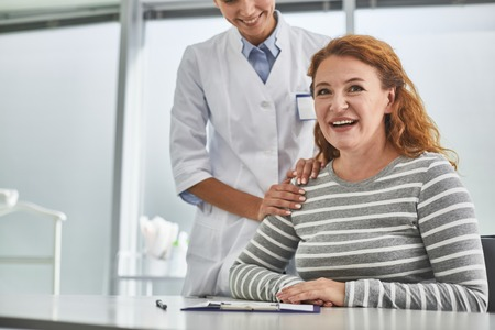 Portrait of beautiful middle-aged lady looking at camera with smile. Cropped young gynecologist touching her shoulder