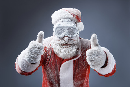 Portrait of bearded old man in Santa costume covered with snow showing thumbs up sign. Isolated on gray-blue background Banco de Imagens