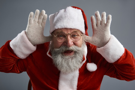 Studio portrait of bearded old man in Santa traditional costume messing around and laughing. Isolated on gray background
