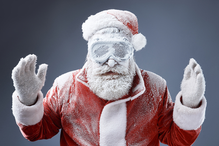 Portrait of bearded old man in Santa costume covered with snow standing on gray-blue background Banco de Imagens