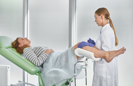 Side view portrait of young gynecologist in white lab coat and sterile gloves holding medical vaginal speculum. Red-haired woman with closed eyes lying in gynecological chair
