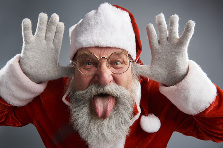 Studio portrait of bearded old man in Santa traditional costume messing around and making funny grimace. Isolated on gray background