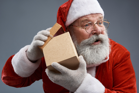 Studio portrait of bearded old man in Santa costume holding christmas present and looking away with opened mouth. Isolated on gray background