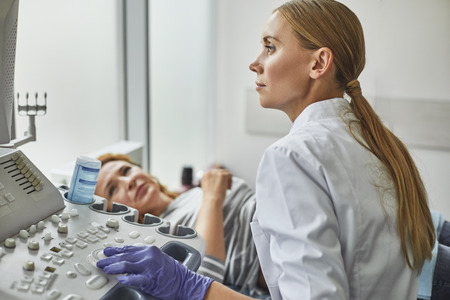 Side view portraits of gynecologist in white lab coat and sterile gloves using ultrasound scanner while examining female patient. Red0haired woman lying on daybed on blurred background