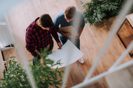 Top view of young men are planning of construction object while standing in office Stock Photo