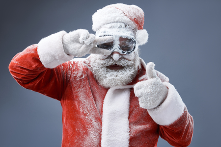 Portrait of bearded old man in Santa costume covered with frost doing approval gesture and keeping hand near eye. He is looking at camera and smiling