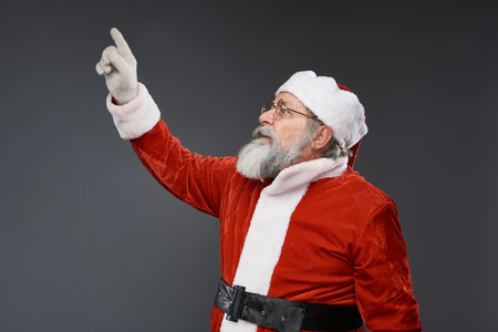 Waist up side view portrait of bearded old man in Santa costume with raised arm standing on gray background