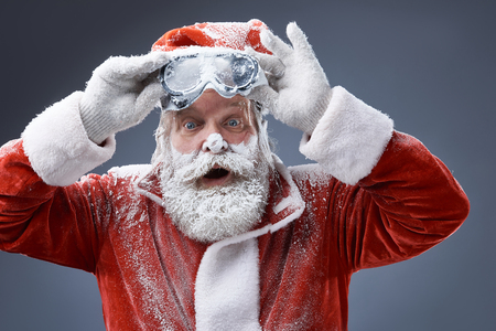 Portrait of bearded old man in Santa costume covered with snow holding goggles and looking at camera with surprised expression. Isolated on gray-blue background Stock Photo