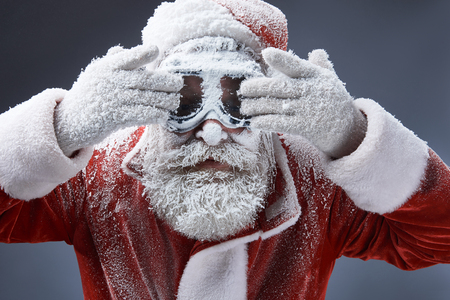 Close up portrait of bearded old man in Santa costume covered with frost trying to clean goggles. Isolated on gray background