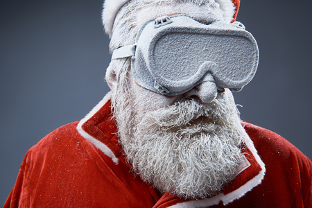 Close up portrait of bearded old man in Santa costume covered with snow. He is wearing protective glasses and looking away