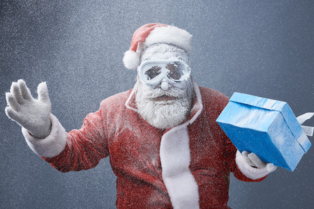 Waist up portrait of bearded old man in Santa costume holding blue box with present. He is wearing protective glasses Banco de Imagens