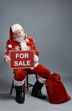 Full length portrait of tired old man in Santa costume with christmas lights resting on chair while being on sale. Isolated on gray background Stock Photo