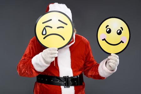Waist up portrait of old man in Santa costume hiding under emoticon icon with sad face while demonstrating carton sign of happiness. Isolated on gray background