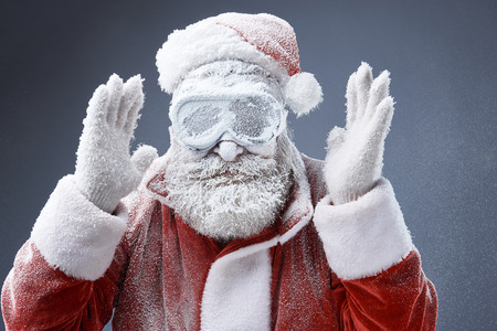 Extreme weather. Portrait of bearded old man in Santa costume covered with snow standing on gray background