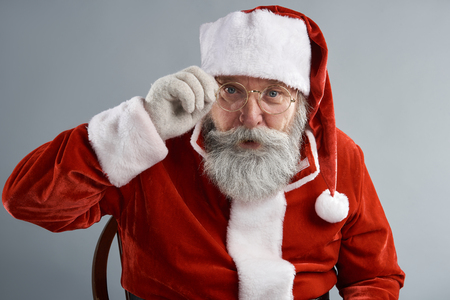 Let me see you. Waist up portrait of bearded old man in Santa costume holding frame of his spectacles. Isolated on gray background