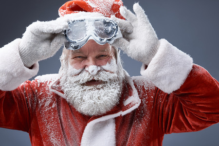 Portrait of bearded old man in Santa costume covered with snow holding goggles and looking at camera with smile. Isolated on gray-blue background