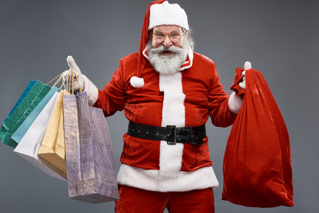 Waist up portrait of bearded old man in Santa costume holding colorful shopping bags and sack with presents. He is looking at camera and laughing