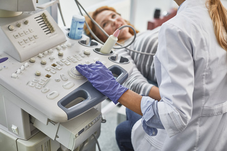 Gynecologist in white lab coat and sterile gloves using ultrasound scanner during medical examination of her patient. Smiling red-haired woman lying on daybed on blurred background