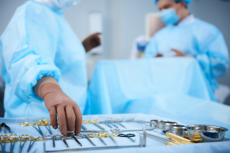 Careful professional surgeon wearing blue medical clothes and taking medical instruments from the table