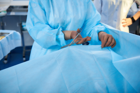Concentrated professional doctor standing with scissors in his hands and cutting the blanket on his patient