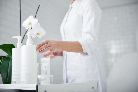 Close up of female hand touching bottle of hair balsam. Cosmetologist wearing white lab coat 版權商用圖片 - 111408965