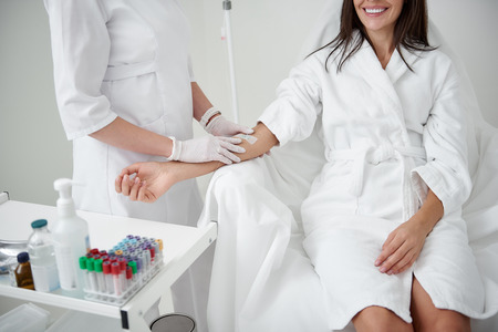 Anti-stress procedure. Cropped portrait of female doctor in sterile gloves preparing lady hand for IV infusion. Brunette girl in white bathrobe smiling Standard-Bild