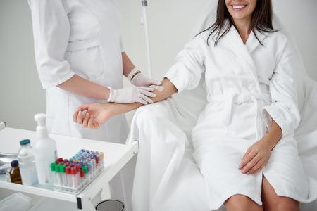 Anti-Stress-Verfahren. Abgeschnittenes Porträt einer Ärztin in sterilen Handschuhen, die die Hand der Dame für die IV-Infusion vorbereitet. Brünettes Mädchen im weißen Bademantel lächelnd Standard-Bild