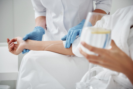 Close up of physician hand in sterile glove checking tube and needle for IV infusion on woman arm. Girl holding glass with lemon water Banco de Imagens
