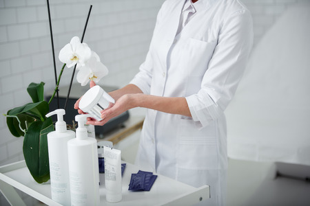 Take care of your skin. Cropped portrait of cosmetologist in white lab coat holding cream jar