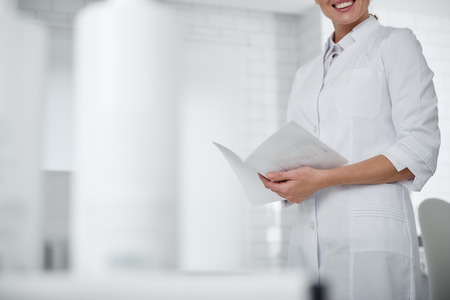 Cropped portrait of young cosmetologist in white lab coat holding brochure and smiling. Copy space on left side