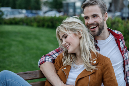 Hilarious lady siting on bench embraced by her boyfriend. He looking aside with bright smile. Copy space on left side Stock Photo