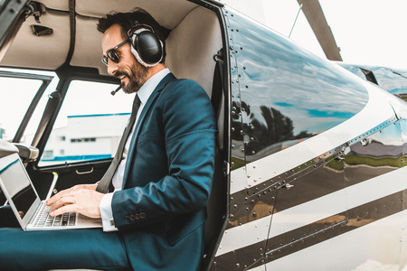 Confident elegant businessman sitting in the helicopter cabin and smiling while using his modern laptop