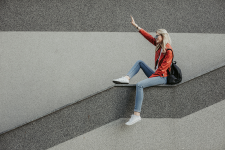 Hilarious girl is waving and looking ahead with smile. Copy space on left side