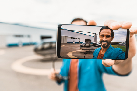 Attractive cheerful man in colorful clothes smiling and holding modern smartphone while taking photos with the helicopter