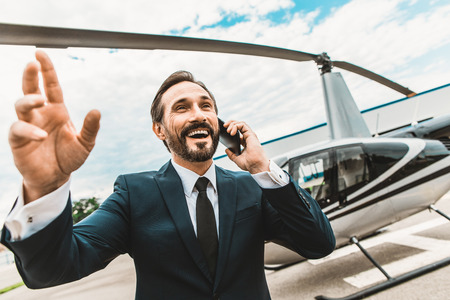 Happy elegant businessman having exciting phone talk and smiling while putting one hand up Imagens