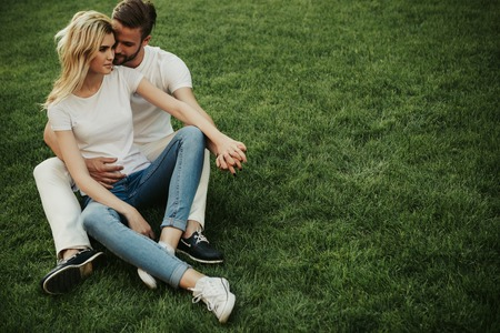 Happy couple is sitting on grass and hugging. They holding hands. Copy space on right side Imagens