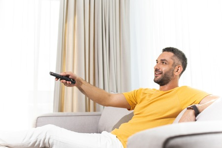 Waist up portrait of young male in good mood is watching TV in his flat while using remote