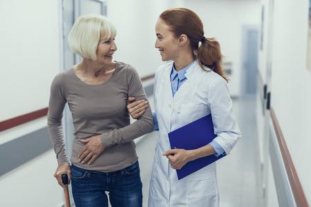 Heureuse dame âgée marche à l'hôpital avec une praticienne. Le travailleur médical aide soigneusement le patient qui s'appuie sur un bâton