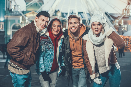 Portrait of positive males and beaming ladies looking at camera while having fun during winter vacation outdoor Stock Photo