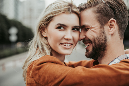Happy twosome embracing at street. She is looking at camera with bright smile while he touching her with forehead Stock Photo