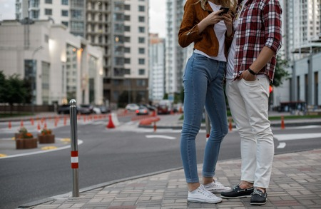 Couple is embracing in city. They wearing casual clothes style. She using handy. Copy space on left side