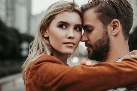 Portrait of happy young lady embracing her boyfriend and looking aside with kind of mystery in her eyes Banco de Imagens