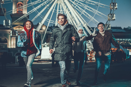 Full length portrait of cheerful males and optimistic ladies gesticulating hands and speaking while moving outdoor during cold evening Banco de Imagens